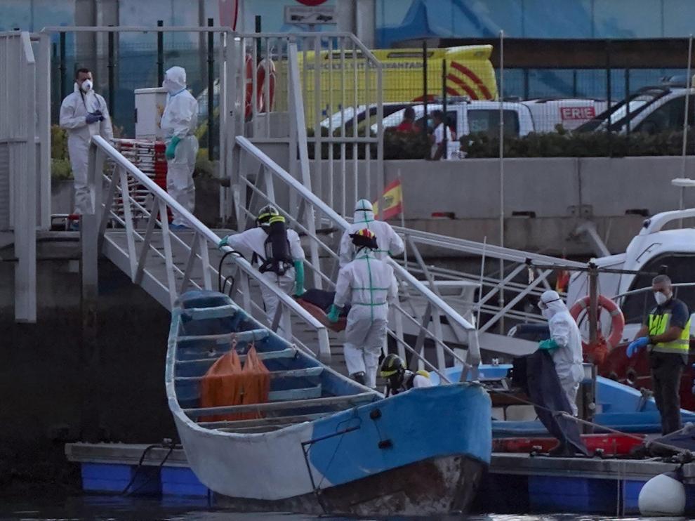 Trabajadores de la Cruz Roja trasladan los cuerpos de inmigrantes fallecidos en un cayuco durante la ruta migratoria hacia Canarias