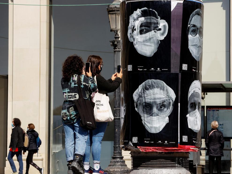 Jóvenes fotografían una iniciativa a favor de los sanitarios.