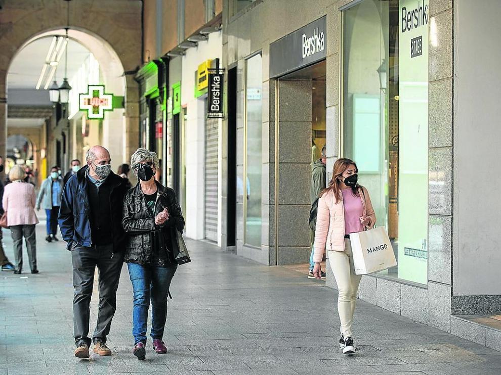 Varias personas pasean con bolsas frente a una tienda de ropa en Independencia, ayer.