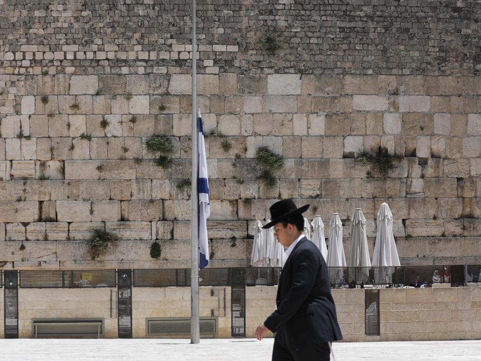 Un judío ultraortodoxo pasa delante de una bandera a media asta en Jerusalén