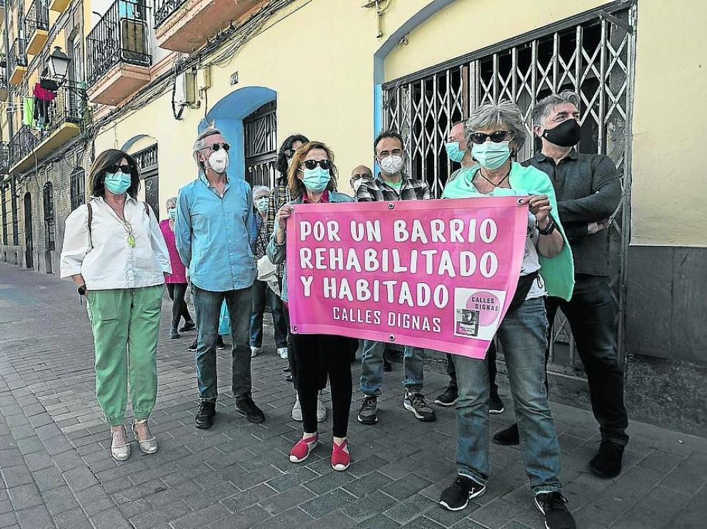 Varios vecinos muestran una de las pancartas de la campaña impulsada por Calles Dignas.