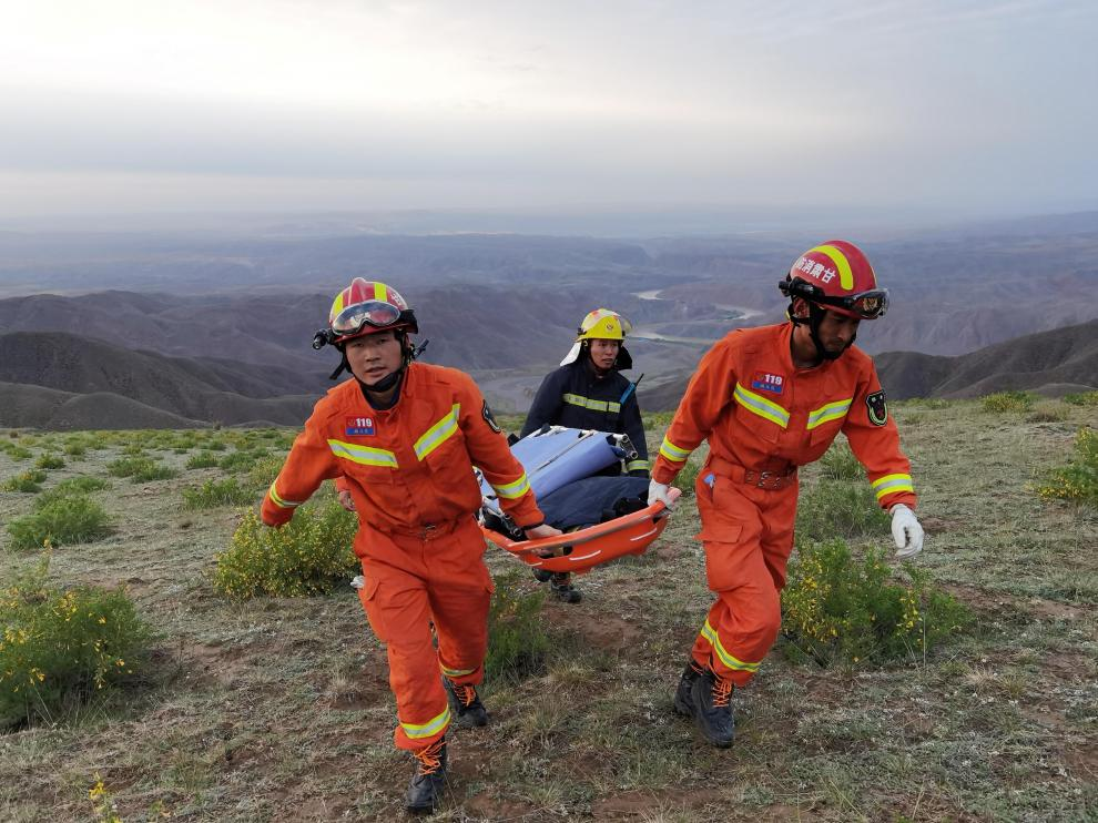 Varios rescatadores evacúan a una persona que participaba en la carrera.