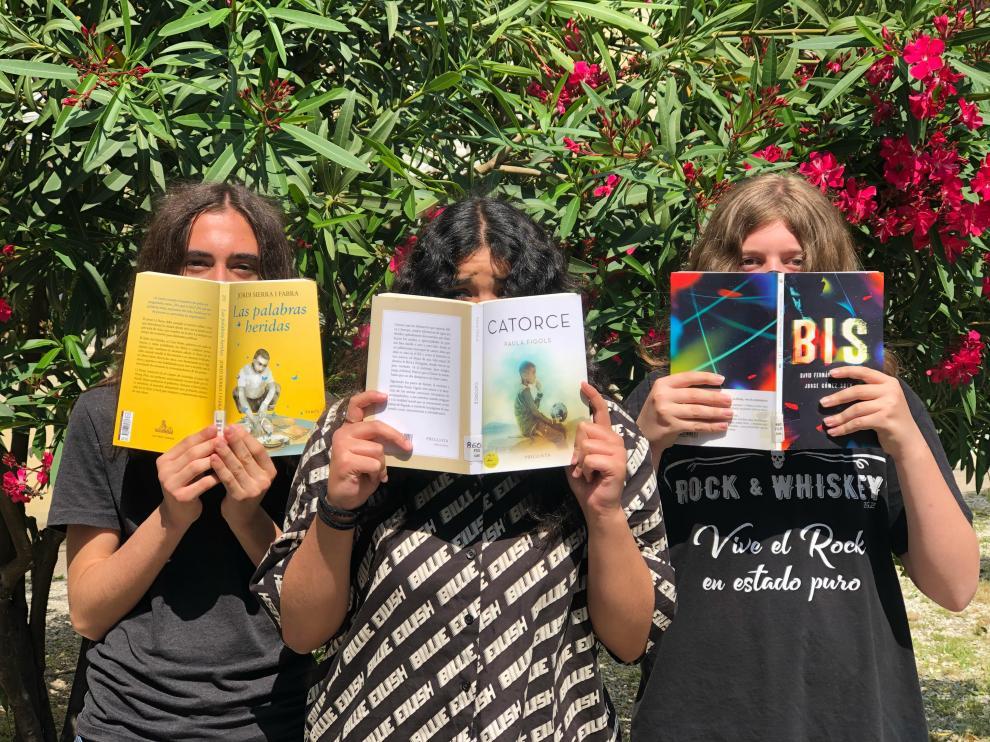 Tres alumnos muestran los libros seleccionados: 'Las palabras heridas', de Jordi Sierra i Fabra; 'Catorce', de Paula Figols; y 'Bis', de Jorge Gómez Soto y David Fernández Sifres