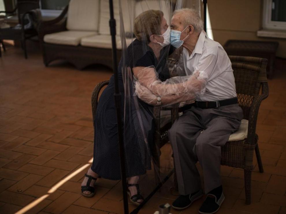 Agustina Cañamero, de 81 años, abraza y besa a su marido, Pascual Pérez, de 84, a través de un plástico en una residencia de Barcelona, el 22 de junio de 2020