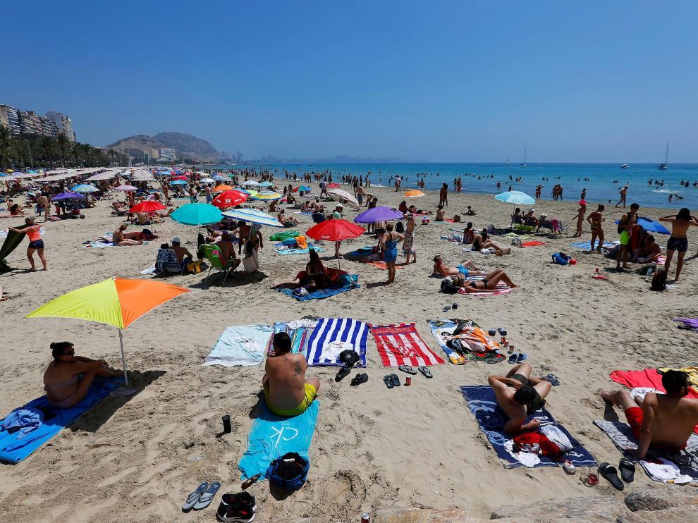 Turistas disfrutan de un soleado día en la playa del Postiguet, este sábado en Alicante.