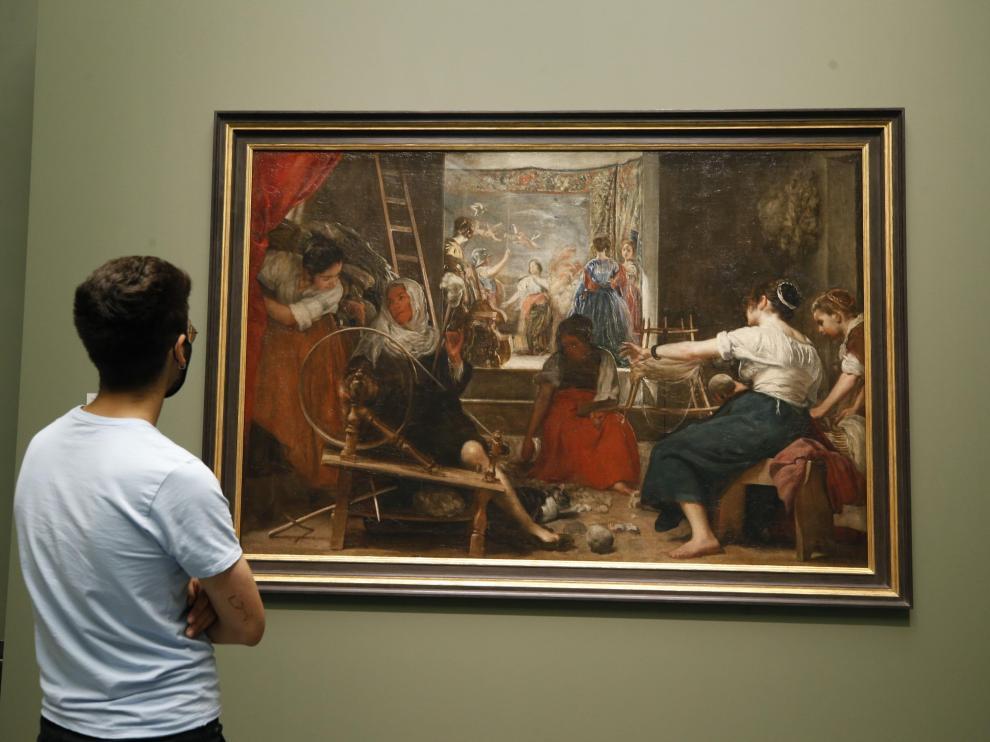 """Un visitante observa """"Las hilanderas"""" de Velázquez, que puede contemplarse desde este lunes en el Museo del Prado tal y como Velázquez quiso que se viera"""