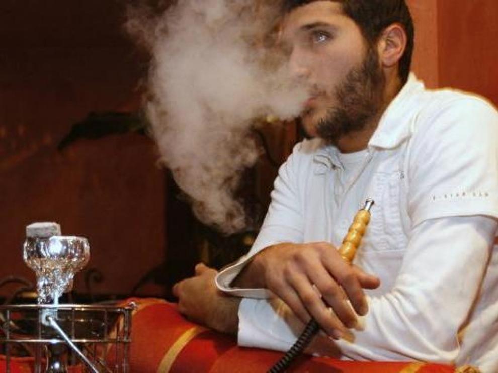 Un joven fuma tabaco con una cachimba en un café de París.