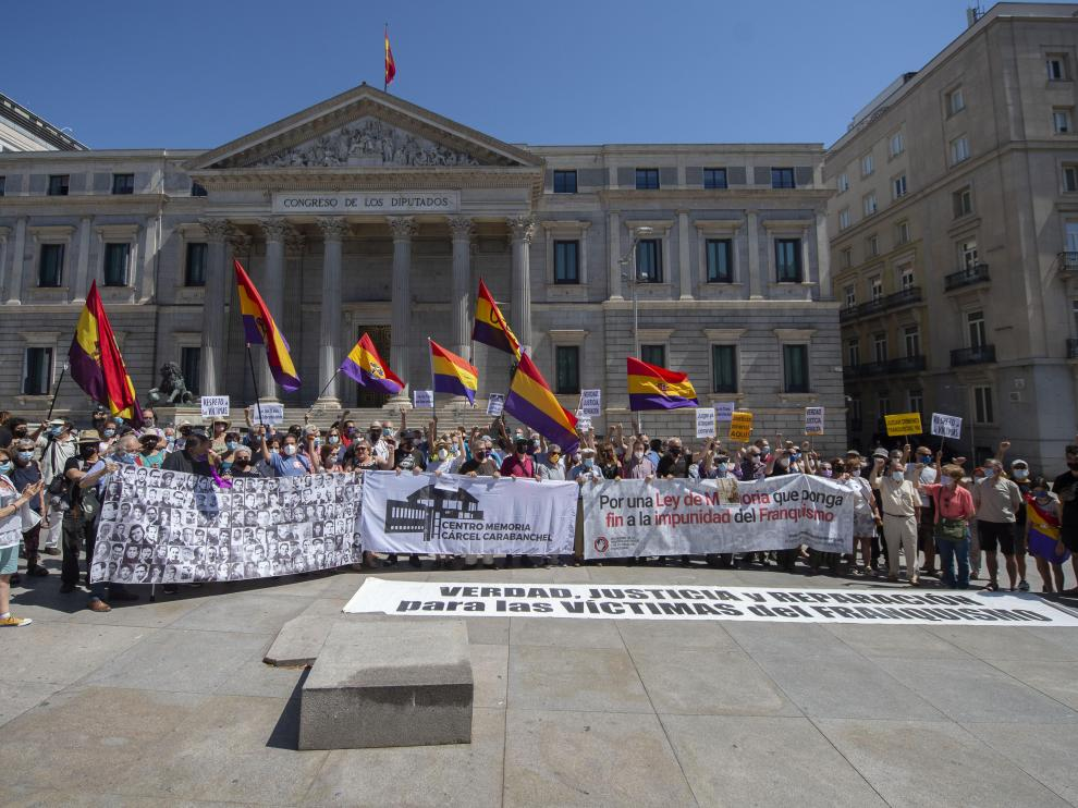 Varias decenas de personas participan en una concentración contra la impunidad del franquismo frente al Congreso de los Diputados, este domingo en Madrid.