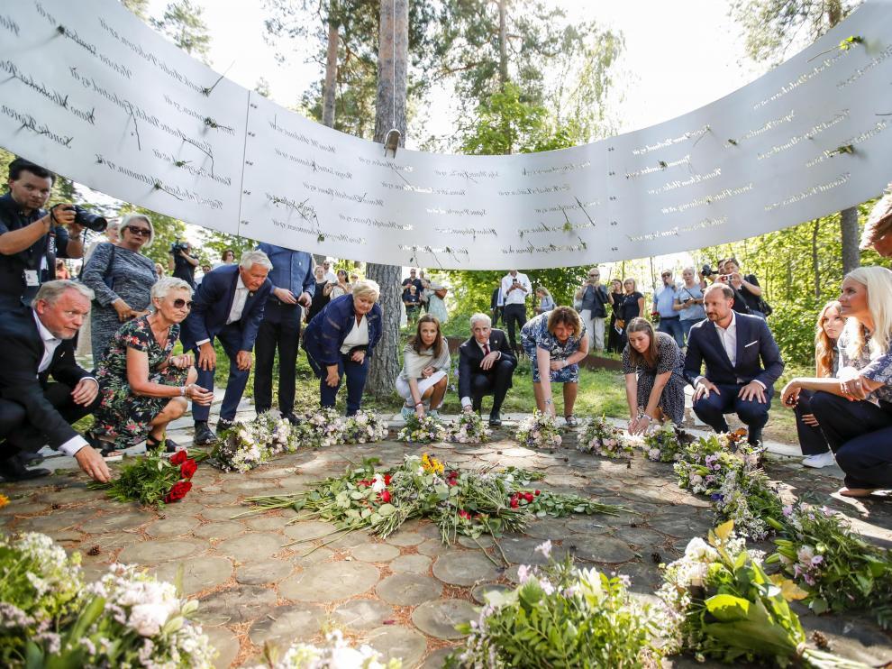 El alcalde de Oslo, Raymond Johansen (i), el príncipe heredero Haakon (4i) y la princesa Mette Marit (2i), entre otras personalidades, en una ofrenda floral en la isla de Utoya, uno de los escenarios de los atentados de hace diez años.