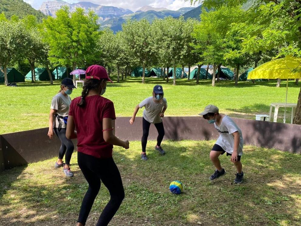 Un grupo de niños jugando con la mascarilla puesta en el campamento de YMCA en Oto (Broto).