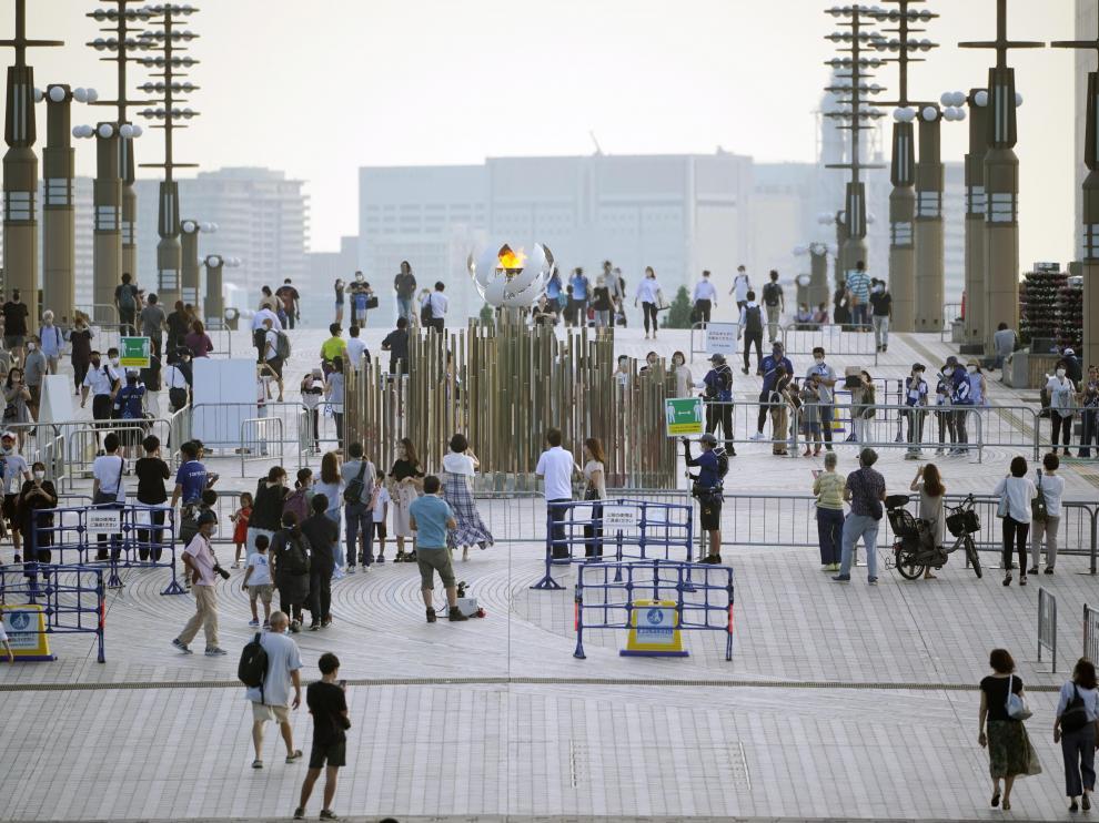 Gente alrededor de la llama olímpica en Tokio.