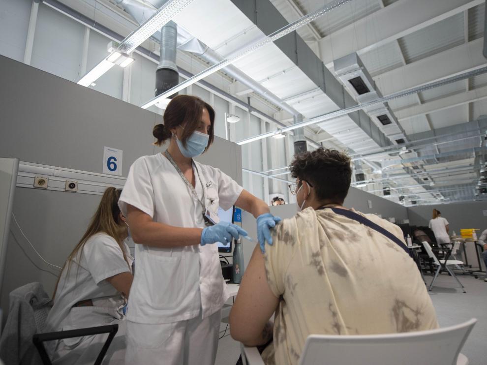 Un joven recibe la primera dosis de la vacuna de Pfizer en el Hospital Zendal.