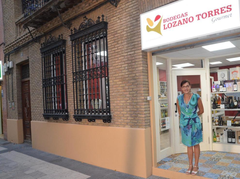 Chus Torres, a la entrada de la tienda, cuya fachada aragonesa está protegida.