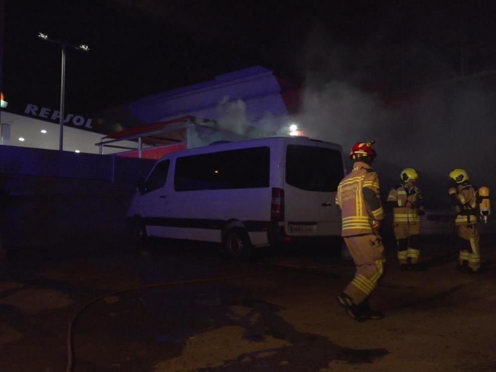 Los bomberos junto a los coches afectados por el fuego en Fraga.