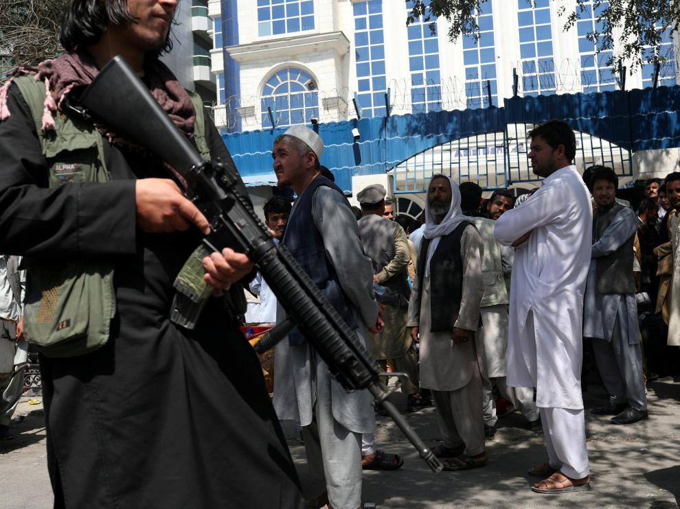 Un miembro de seguridad talibán vigila la fila de personas frente al Banco Azizi de Kabul, en Afganistán