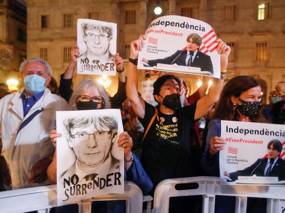 Varias personas sostienen retratos del expresidente de la Generalitat Carles Puigdemont en Barcelona.