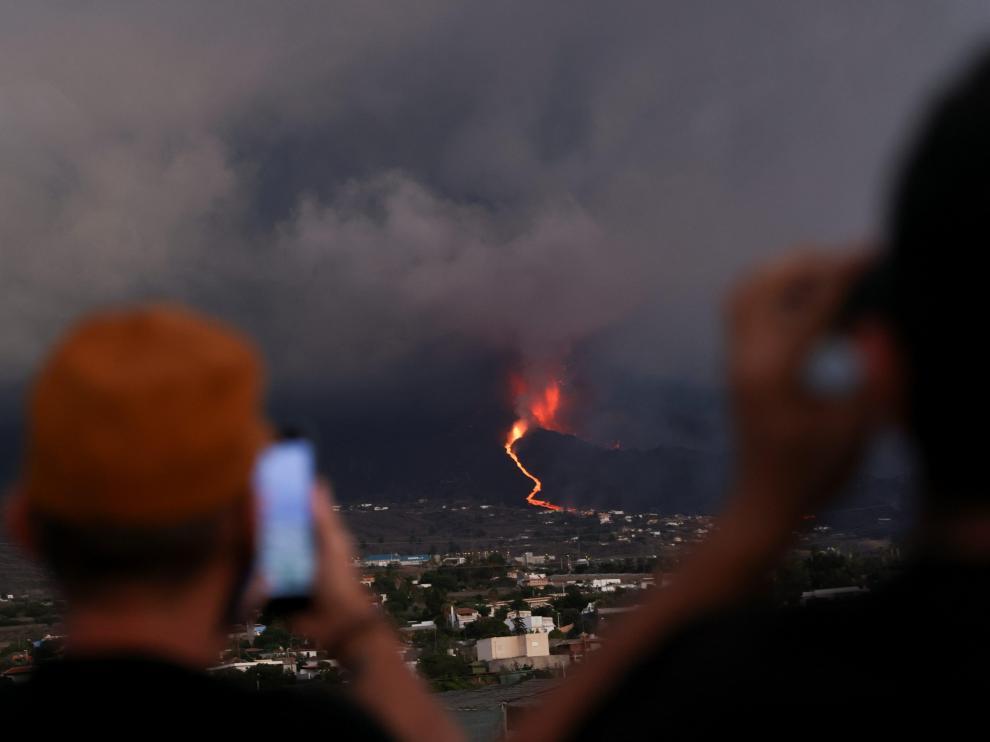Dos personas miran cómo desciende la lava por la ladera del volcán