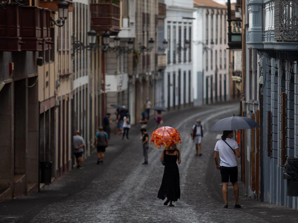 Varias personas caminan con paraguas para protegerse de la ceniza en Santa Cruz de La Palma