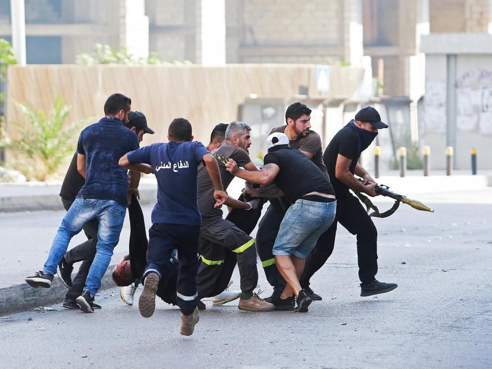 ATTENTION EDITORS - SENSITIVE MATERIAL. THIS IMAGE MAY OFFEND OR DISTURB Men run to rescue a person shot while preparing to fire a rocket-propelled grenade, during a gunfire in Beirut, Lebanon October 14, 2021. REUTERS/Aziz Taher[[[REUTERS VOCENTO]]] LEBANON-CRISIS/BLAST