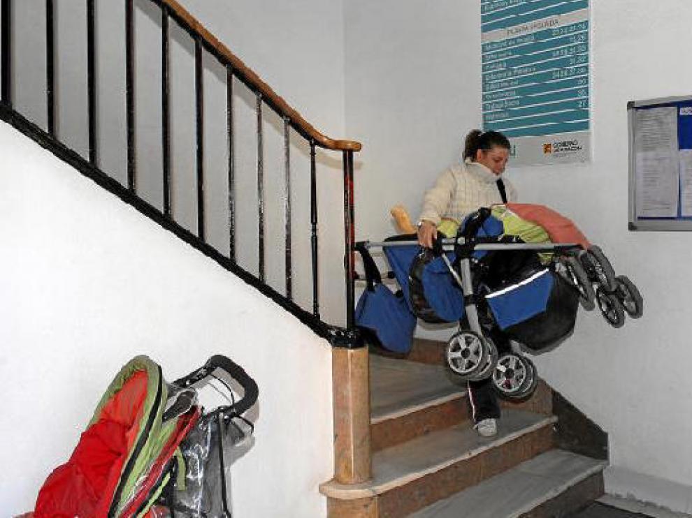 Una mujer desciende por la escalera principal del centro de salud con un cochecito de bebé en brazos.