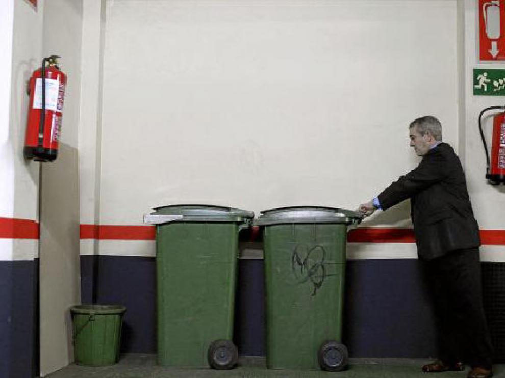 Ricardo Gimeno, conserje del paseo de Sagasta 20, guarda los cubos en el garaje.