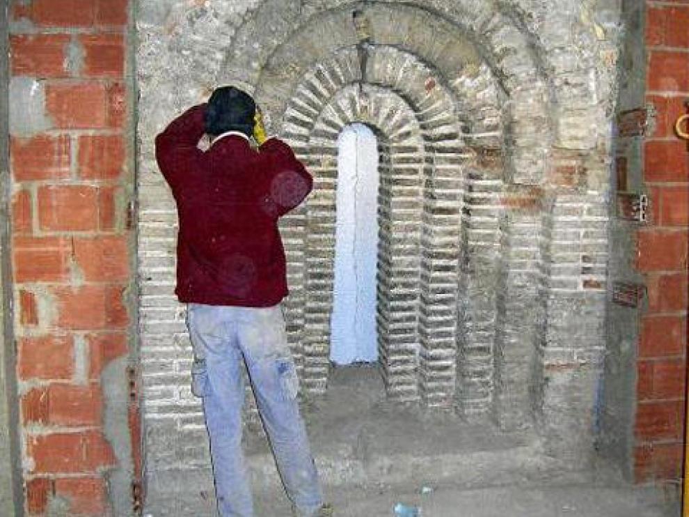 Un obrero trabaja en la rehabilitación del arco aparecido en la que será la casa del párroco