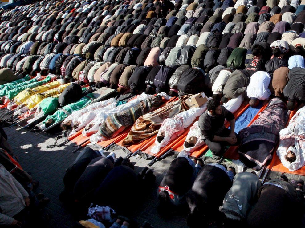 Numerosos palestinos rezan junto a los cuerpos de los 43 palestinos asesinados en un ataque israelí