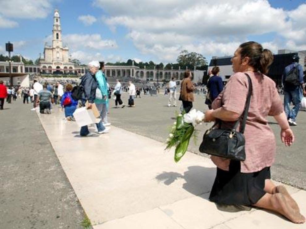 Una mujer, de rodillas frente al santuario de Fátima