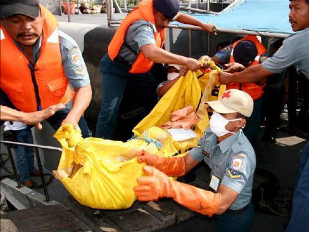 Efectivos de rescate transportan un cadáver en el puerto indonesio de Surabaya.
