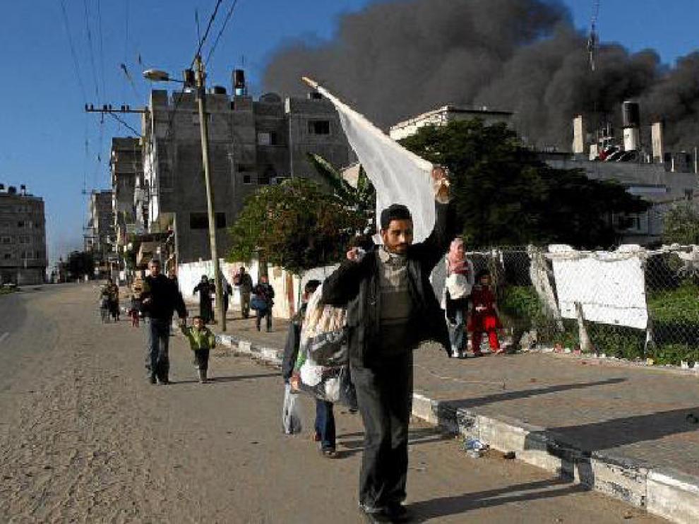 Un palestino sujeta una bandera blanca al abandonar su casa en la franja de Gaza.