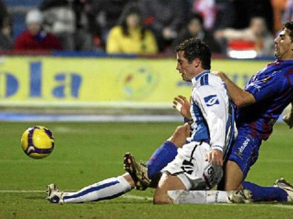El delantero del Huesca Roberto García trata de anticiparse a un futbolista rival