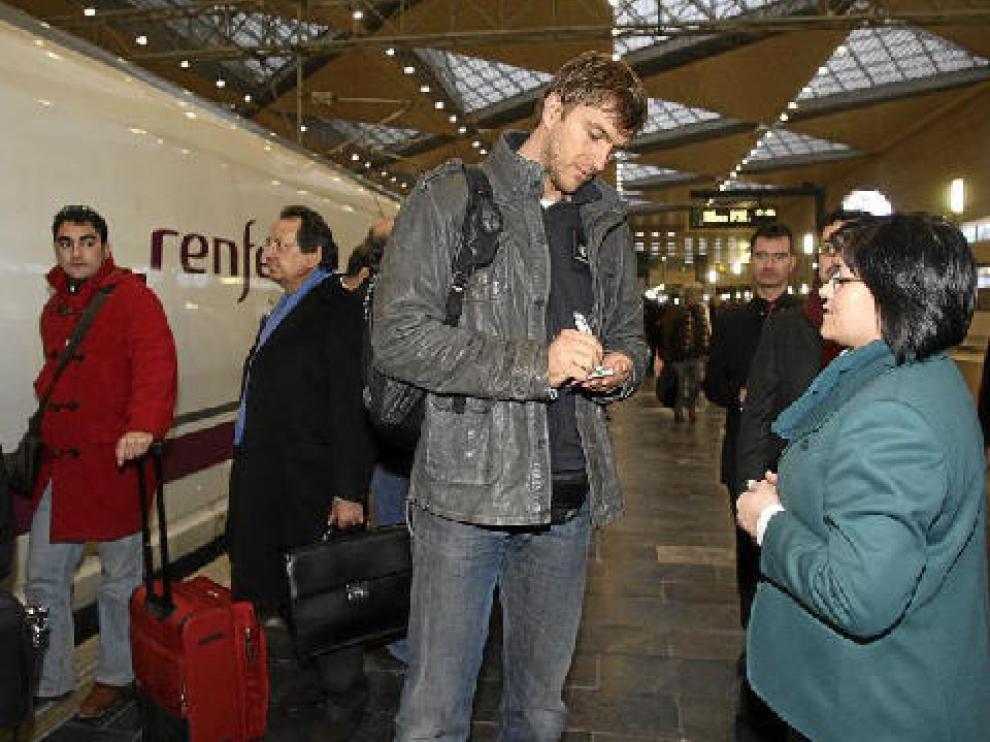 Zizic firma un autógrafo a una empleada de la estación de Delicias a su llegada a Zaragoza.