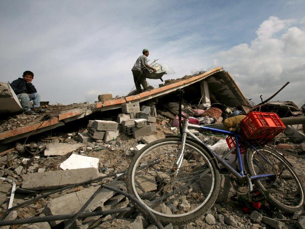 Varias personas, entre los escombros de la que fuera su vivienda, destruída durante la ofensiva israelí