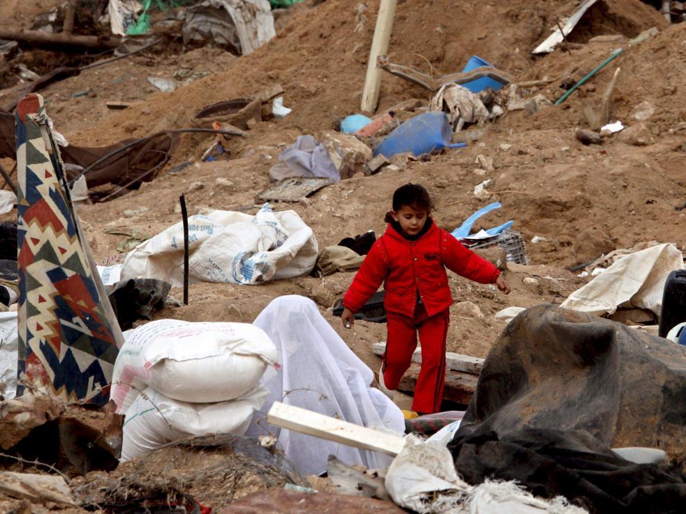 Una niña se dirige al colegio entre los escombros de la guerra