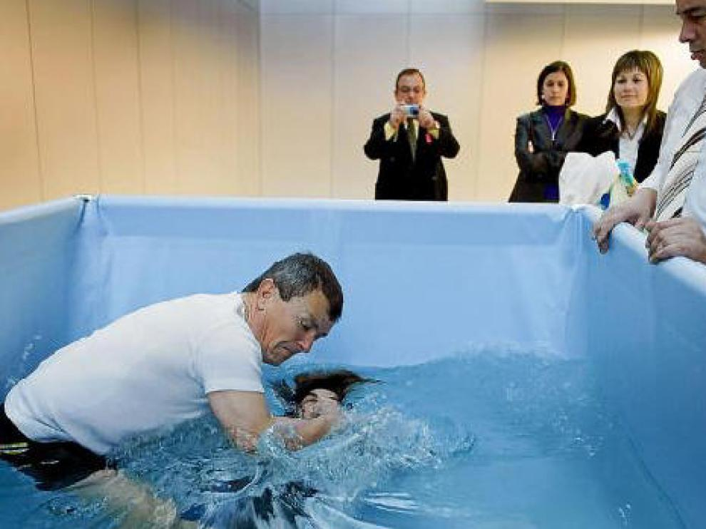 Liseth Jacome recibe el bautismo rodeada por otros Testigos de Jehová.