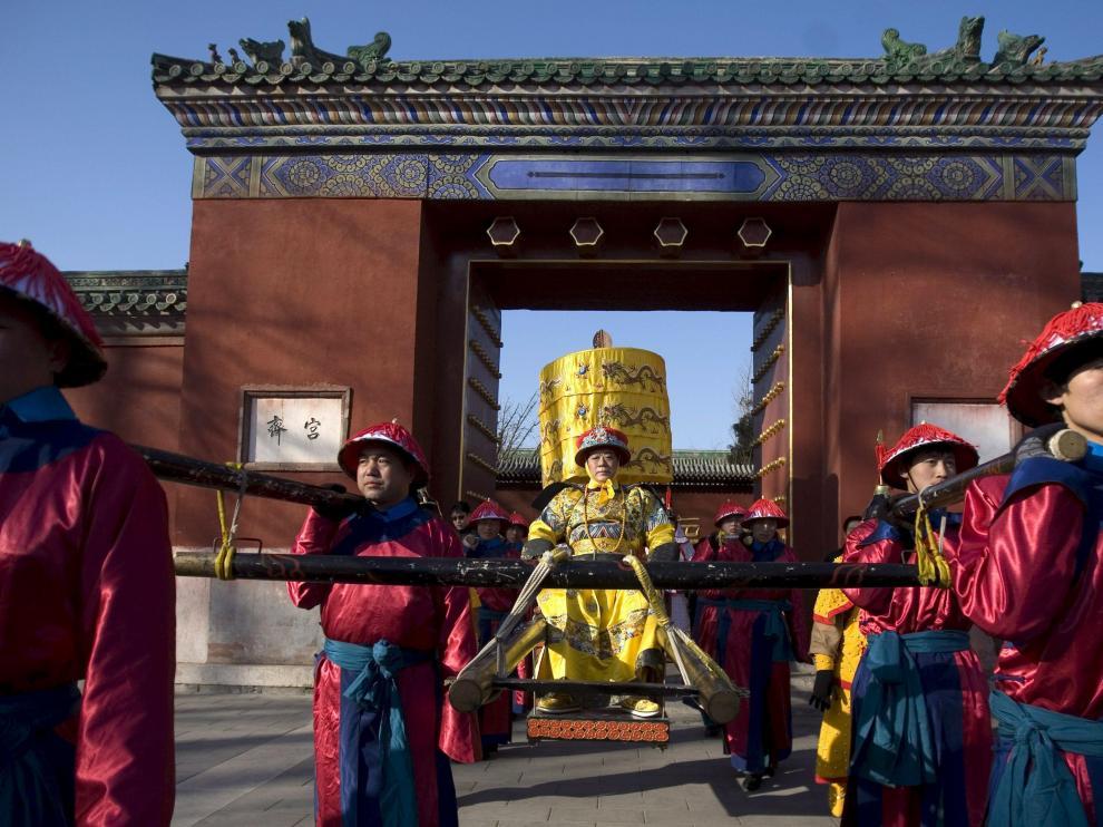 Varios actores vestidos con trajes típicos participan en la representación de un sacrificio imperial en el Parque Ditan de Pekín