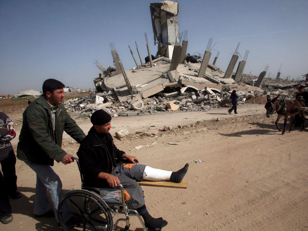 Un herido, en silla de ruedas, visita una zona de Gaza destrozada por las bombas israelíes