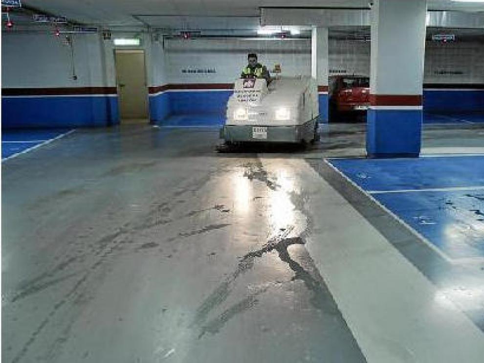 Un operario de la empresa que explota el parquin limpia el agua que entra a través del techo y las paredes.