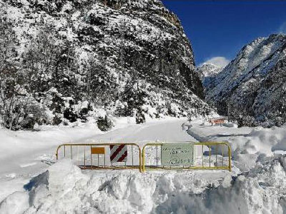 Una valla y un cartel escrito a mano indican, dos kilómetros antes del alud, que el acceso está cerrado.