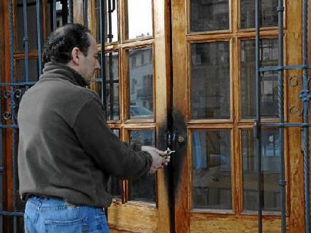 Un hostelero de Rubielos muestra los daños que hicieron los ladrones, que quemaron la puerta.