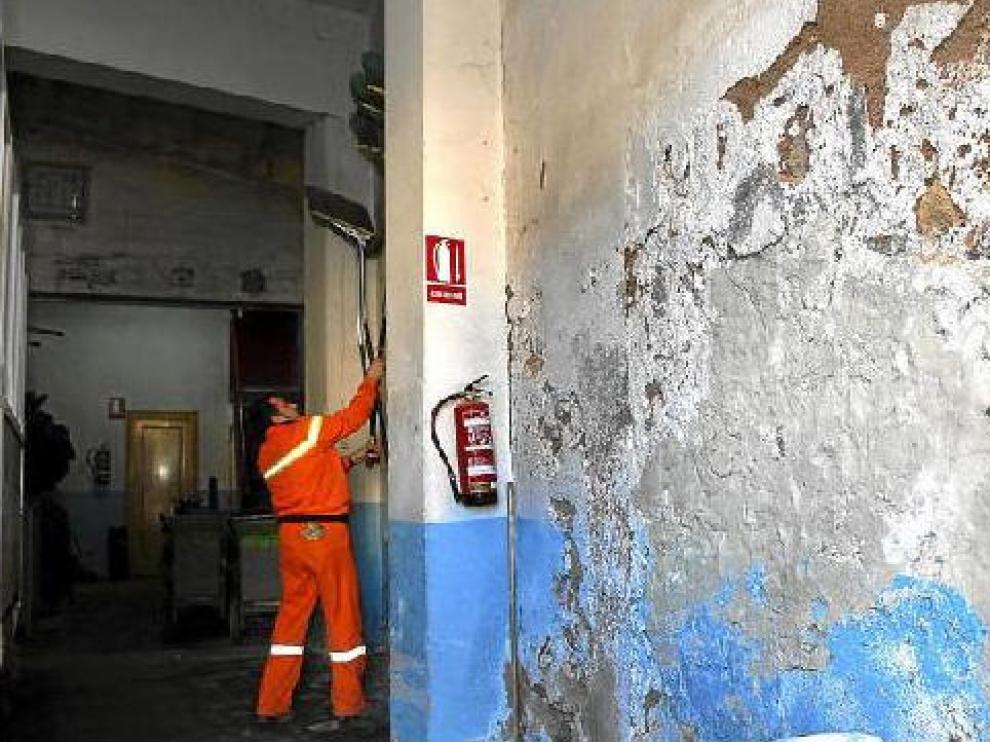 Las paredes del local destinado a los servicios de limpieza del ayuntamento están cubiertas de desconchones y humedades.
