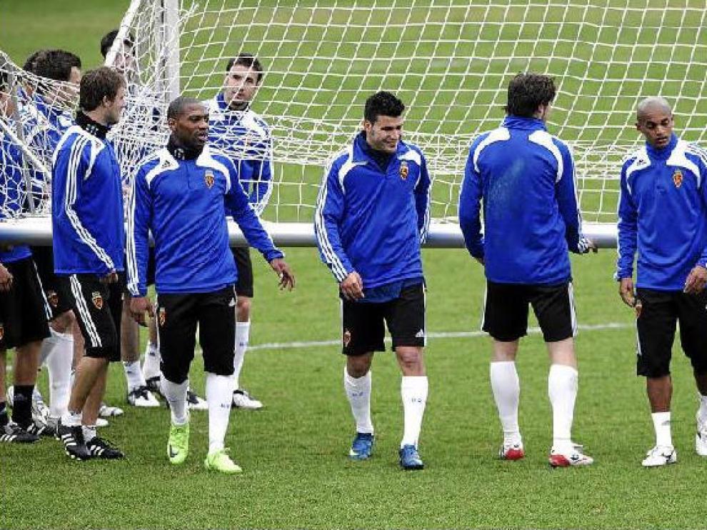 Songo'o, Braulio y Ewerthon, entre otros jugadores de la plantilla que se ocupan de trasladar una portería, en el entrenamiento de ayer.