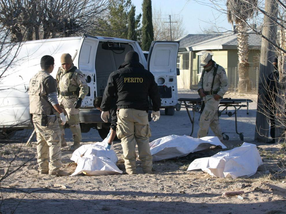 Peritos forenses y miembros del Ejército mexicano realizan el levantamiento de los cadáveres