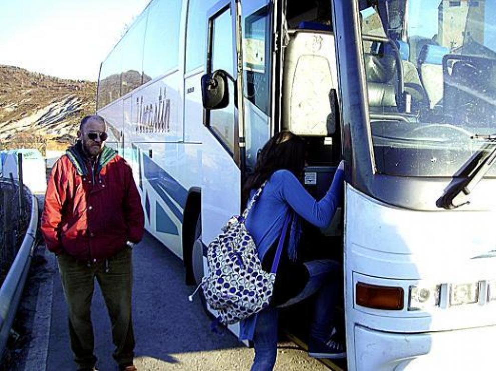 Una chica sube al autobús escolar en la parada de Larrés.