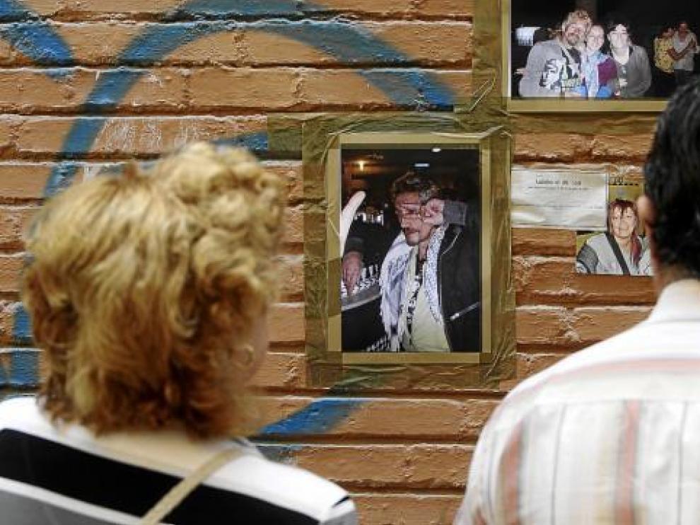 Dos vecinos de La Magdalena miran fotos de la víctima que sus amigos colocaron en su recuerdo.