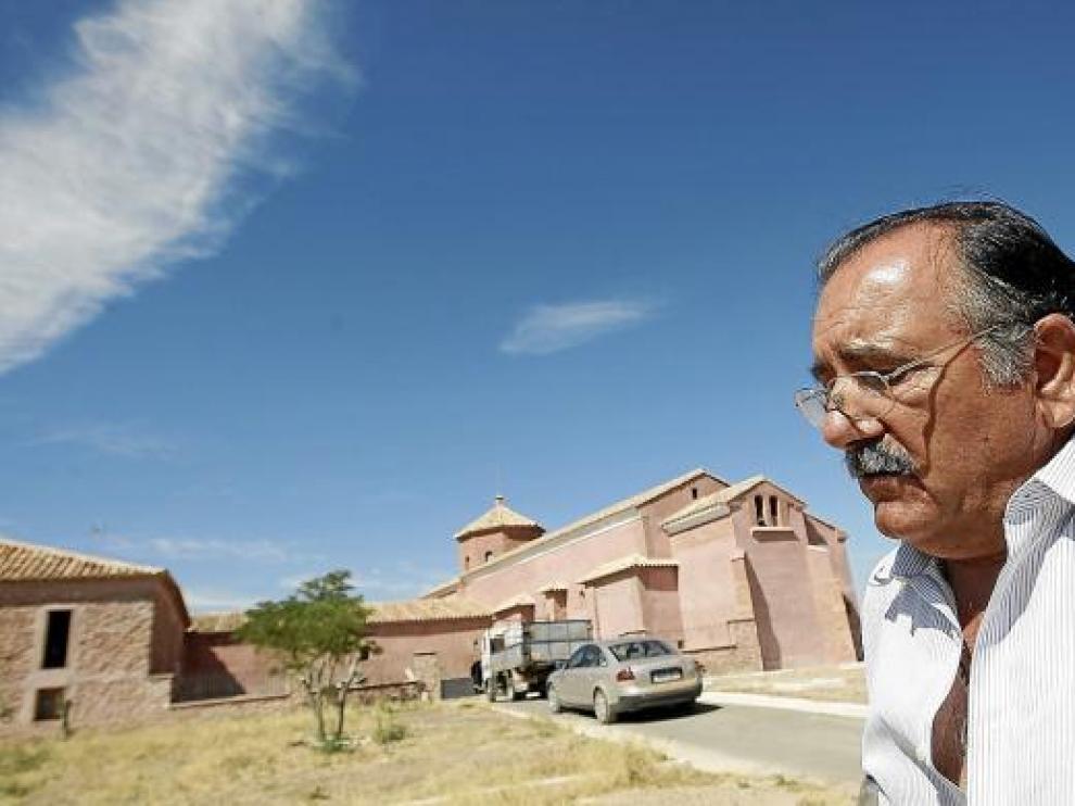 El alcalde de Plenas, Baltasar Yus, frente al albergue y la ermita de El Carrascal.