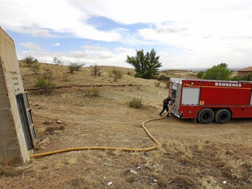 Los bomberos almacenan el agua en el depósito de Collados, barrio de Calamocha.