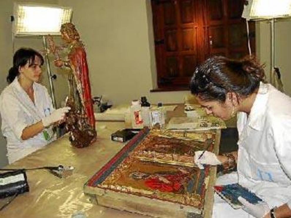 Dos restauradores, en pleno proceso de recuperación de distintas obra de pintura y escultura