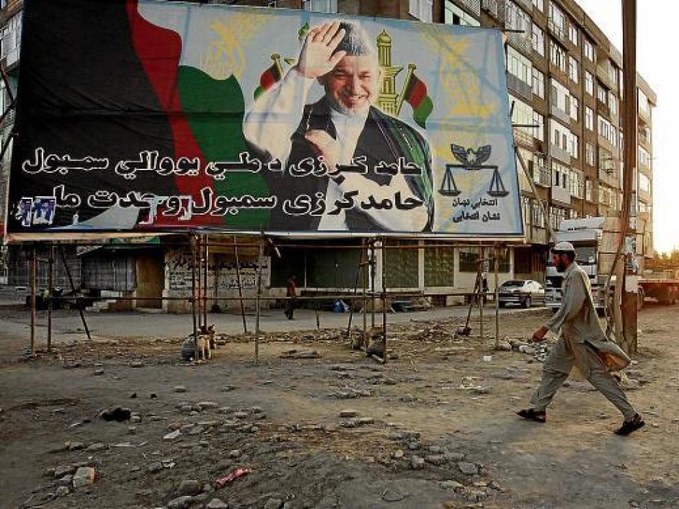 Un hombre pasa frente a un cartel electoral del presidente afgano Karzai, en Kabul.