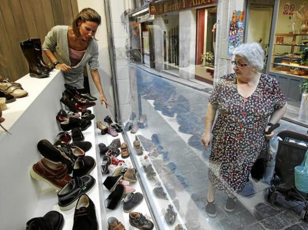 Ainhoa Labadía arregla el escaparate de su zapatería infantil, ayer, en la calle de Ramiro El Monje.